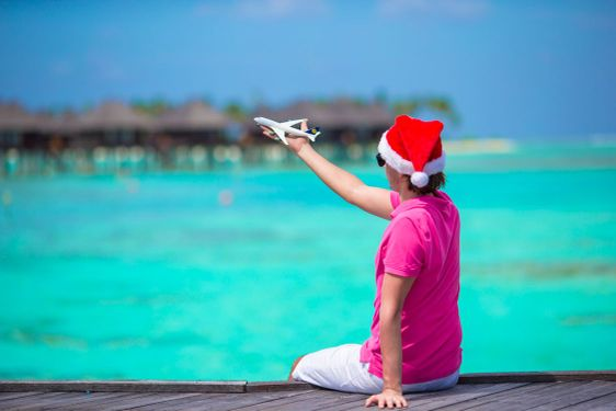 Young man in santa hat on white beach with miniature of...