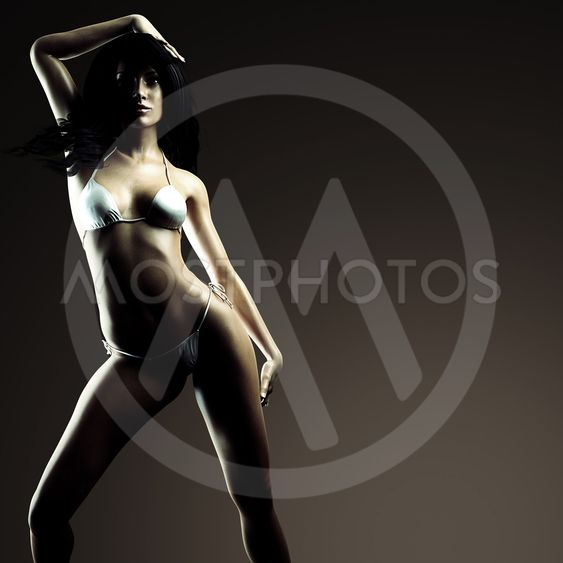 Sexy brunette bikini woman posing in dark studio