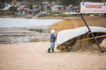 Pojke på strand vid räddningsbåt
