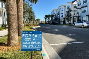 A real estate For Sale sign in front of a home that is...