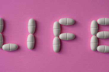 """White pills or tablets arranged with the text """"life"""""""