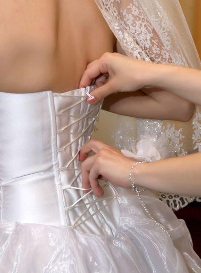 Girlfriend tightens corset bride