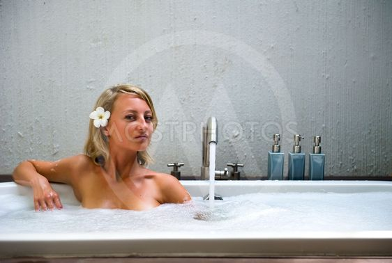 Beautiful young woman taking a bubble bath