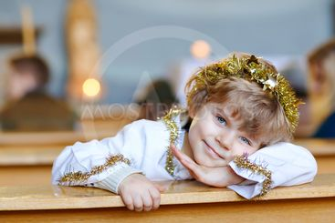 Beautiful little kid boy playing an angel in Christmas...