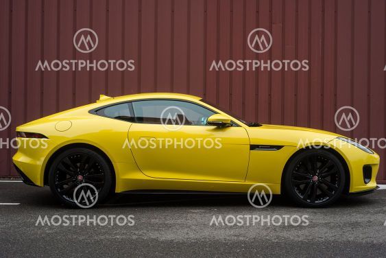 Profile view of yellow Jaguar F-Type parked in the street