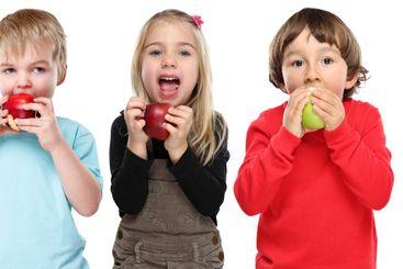 Group of kids children eating apple fruit autumn fall...