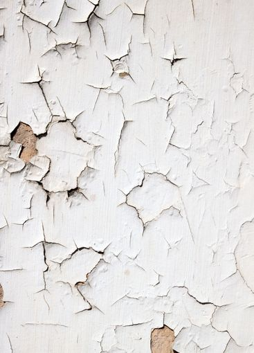 Old flaky white paint peeling off a wall.
