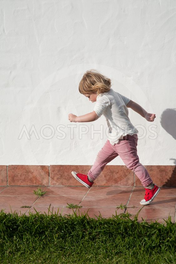 walking little child in garden over white wall