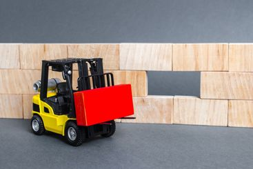 A forklift carries a red block to insert into a wall...