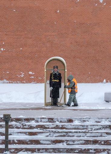 A utility worker cleans snow next to a soldier at a post...