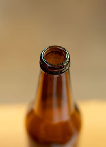 Closeup view of brown glass bottle, focus on the rim