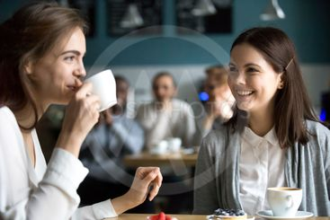 Pretty girls having fun in cafe drinking coffee