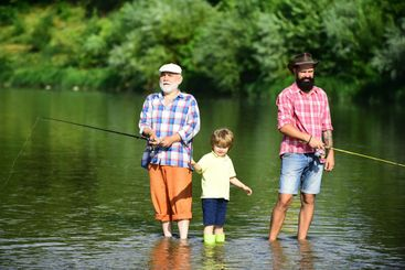 Family bonding. Grandfather, father and grandson fishing...