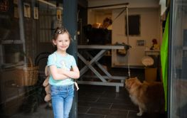 little cute girl standing in front of beauty salon for...