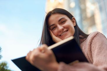 Close up portrait of a charming lady reading outdoors