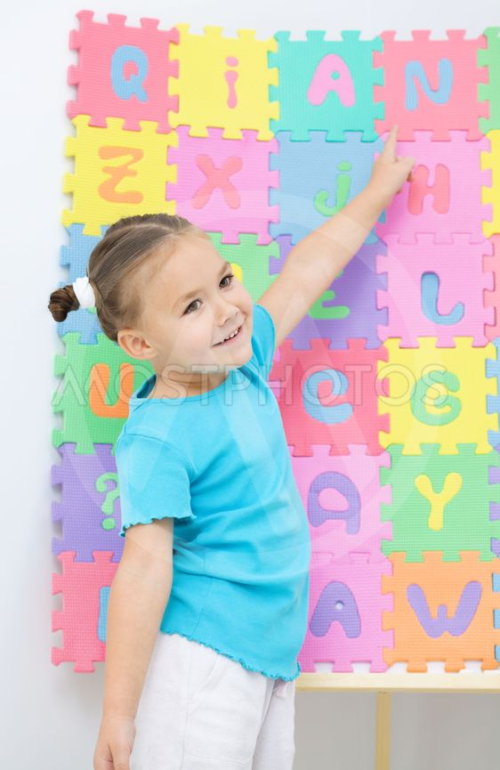 Little girl is pointing at letter N