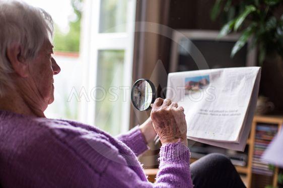 Senior woman reading morning newspaper, sitting in her...