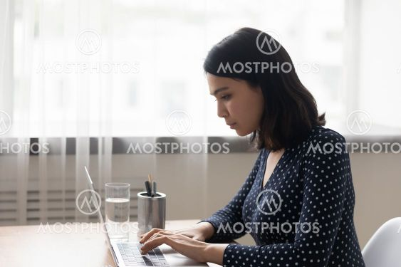 Close up confident Asian woman working on laptop, typing