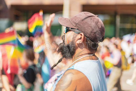 Man with beard and cap from the side at the pride parade...