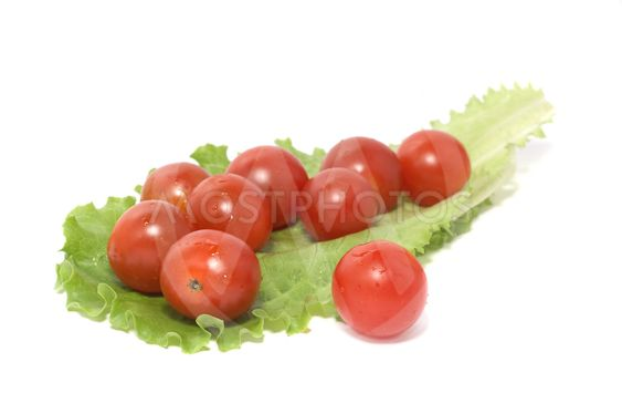 Tomater og et ark med salat på hvid baggrund