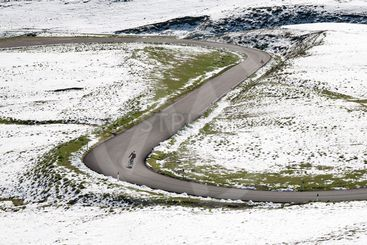 Cyclist goes downhill along a mountain road in a snowy...