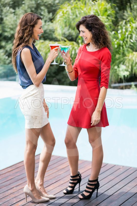 Cheerful female friends toasting cocktails