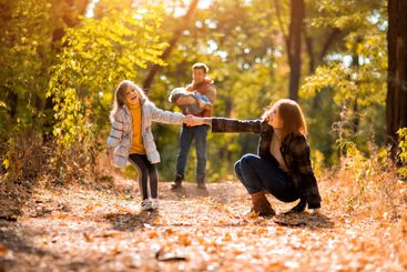 mother and daughter running and falling in autumn Park....