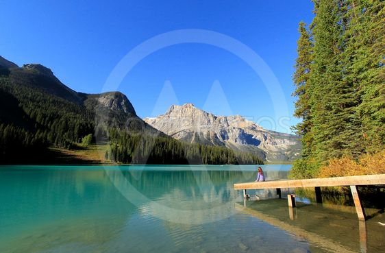 Young woman sitting on a pier at Emerald Lake, Yoho...