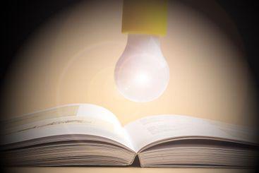 a glowing light bulb over an open book
