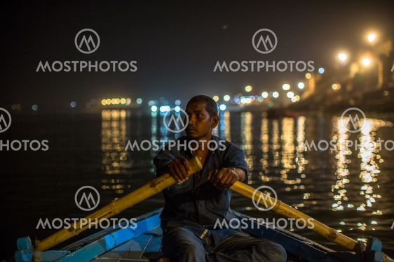 Boatmen on the Ganga river at night. Varanasi is one of...