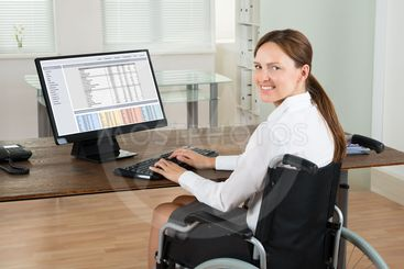Businesswoman On Wheelchair Using Computer In Office