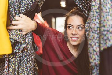 Beautiful girl at clothes shop looking for a dress