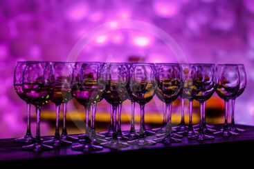 Stemware in purple light. Many glass of wine on a table....