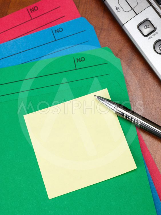 close up image of files with pen and adhesive note