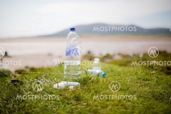 Couple of Littered Plastic Bottles on Grass with a...