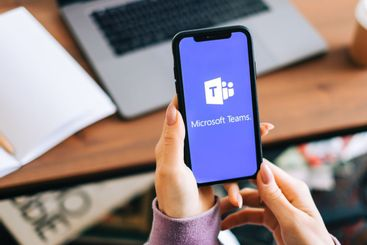Hand holding iPhone with Microsoft Teams video call app...