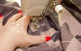 Woman taylor is working on a sewing machine closeup