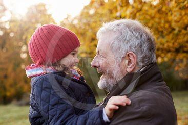 Grandfather Cuddling Granddaughter On Autumn Walk