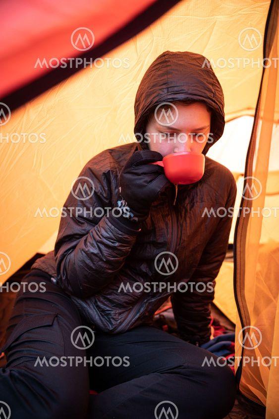 tjej dricker te i tält