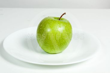 Green Apple with water drops in a plate