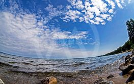 rocky shore of the morning lake with blue sky with light...