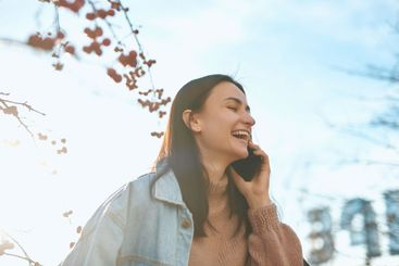 Pleasant female talking by cellphone and laughing