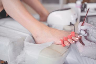 Pedicurist doing white nail polish on client legs using...