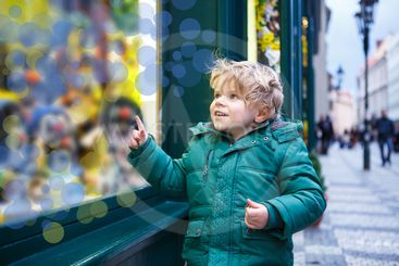 Adorable little boy looking through the window at...
