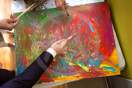 Closeup of people mixing colorful paints on canvas