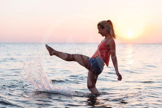 Young woman enjoying sea and sunset