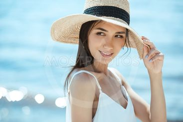 selective focus of attractive asian woman in straw hat...