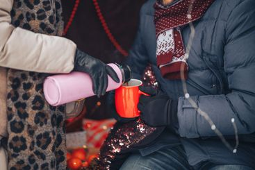 Thermos and cup of tea in hands