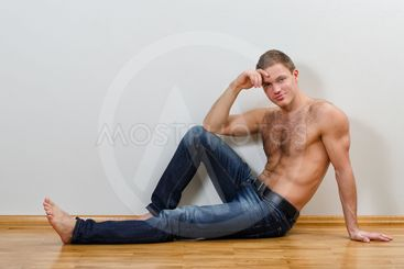 Handsome guy in jeans with bare torso sitting on the...