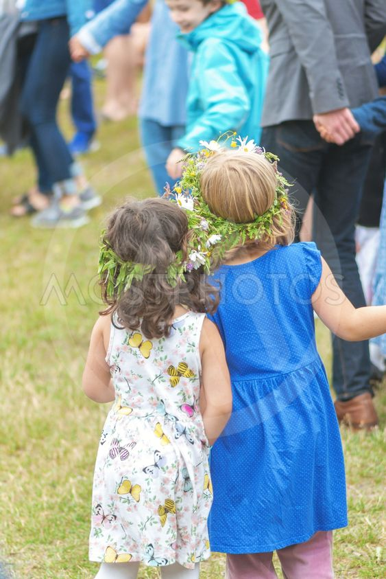 People celebrating midsummer with dance around the maypole